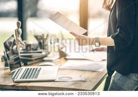 Cropped Image Of Young Businesswoman Holding Paperwork While Standing Near Her Desk At Office