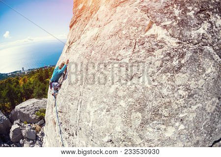 A Rock Climber On A Wall.