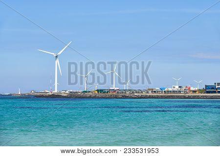 Landscape Of Coast With Wind Generator In Woljeong-ri, Jeju, Korea. Jeju Island Is Famous For Beauti