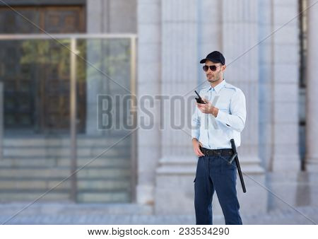 Digital composite of security guard with sun glasses and walkie-talkie guarding the door