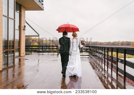 Young Couple Under Umbrella In The Autumn On Rainy Day Weather. Lovely Couple In Love With Umbrella
