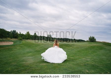 Full length body portrait of beautiful bride in fashion white wedding dress with feathers running away through green golf course, back view. Runaway bride, copy space poster