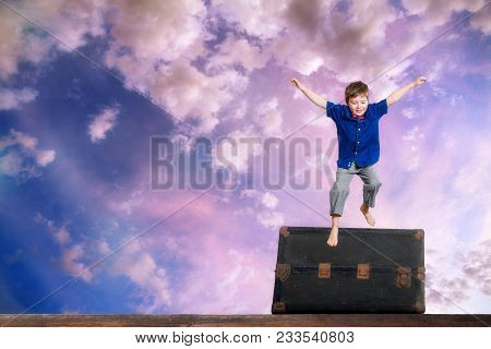Composite Piece Of A Young Boy Leaping Or Jumping Over An Old Steamer Trunk In Front Of A Colorful,