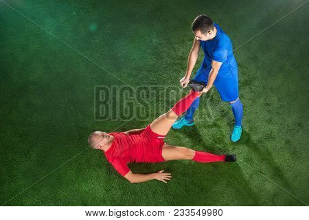 Male Soccer Player Suffering From Leg Injury On Football Green Field At Stadium. The Professional Fo