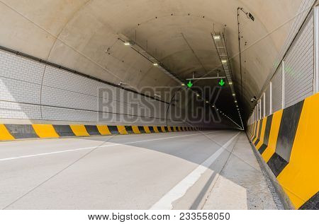 Two Lane Highway Tunnel Of White Concrete With Florescent Lights And Green Arrows On Ceiling And Ele