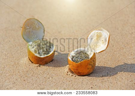 Two Orange Open Passion Fruit With Seeds. Passion Fruit Closeup On The Beach, On The Sand And On The