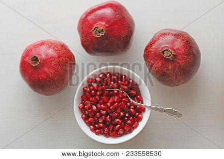 Grains Of Red Ripe Pomegranate Lie In A White Bowl With A Spoon. Big Ripe Red Granets Or Garnets. Fr