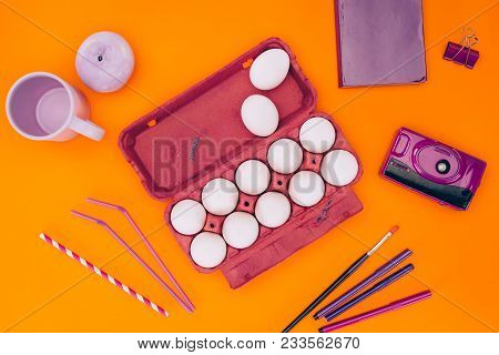 Elevated View Of Chicken Eggs In Egg Tray And Felt Tip Pens For Easter Painting Isolated On Orange