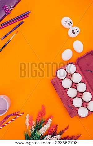 Top View Of Chicken Eggs In Egg Tray And Felt Tip Pens For Easter Painting Isolated On Orange