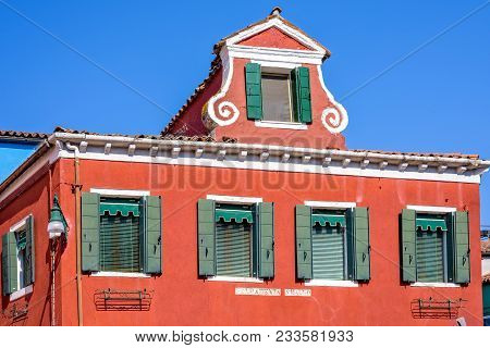 Daylight View To Vibrant Red Facade Of A House With Ornaments