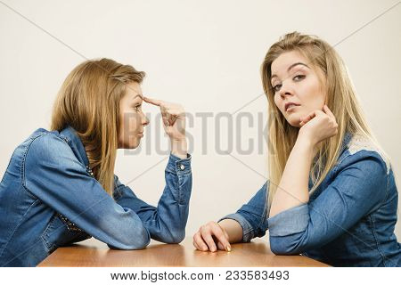 Woman Saying Bad Things About Her Over Confient Female Friend. Pointing At Forehead, Stupidity Gestu