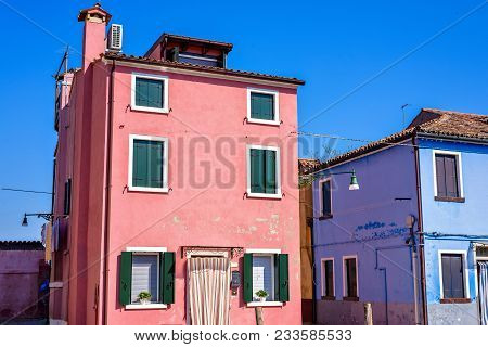 Daylight View To Vibrant Colorful Pink And Blue Houses Facades