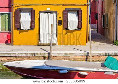 Daylight View To Boat Parked In Local Canal Near Sidewalk