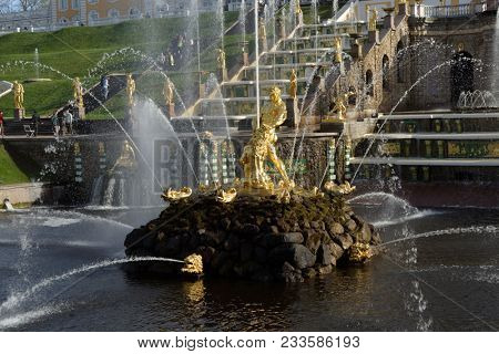 PETERHOF, ST. PETERSBURG, RUSSIA - MAY 7, 2016: Tourists walking around the Sea canal and the Grand Cascade against Grand Palace. The cascade was built in 1715-1724
