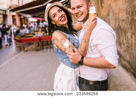 Happy Lovely Couple Eating An Ice Cream On A Date. Smiling Couple In Love Outdoors