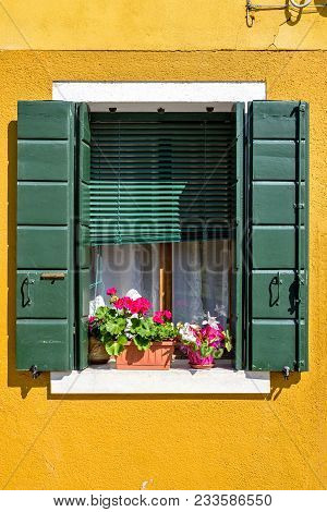 Daylight View To Yellow Facade Building Window With Shutters