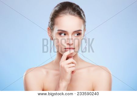 Woman Touching Lower Lip And Looking Aside Slyly
