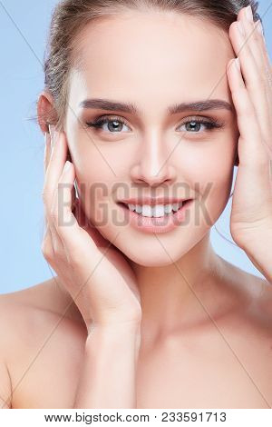 Smiling Woman Touching Face With Both Hands