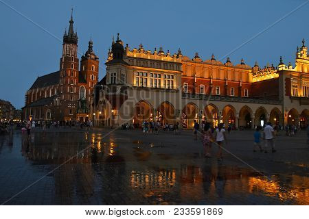 Low Angle Night View Of Main Market Square With Town Hall And Church Of Our Lady Assumed Into Heaven