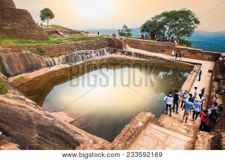 SIGIRIA, SRI LANKA - DEC 26, 2016: Tourists walking around pool in the royal garden palace complex Sigiriya Rock, Dambulla on Dec 26, 2016, Sri Lanka. Sigiriya is a UNESCO World Heritage site.