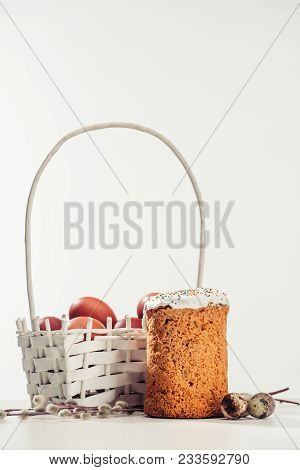 Decorative Basket With Painted Chicken Eggs, Easter Cake, Quail Eggs And Catkins On Grey