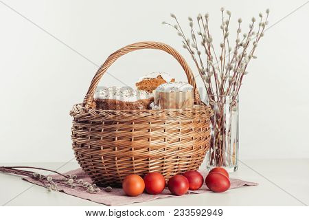 Basket With Easter Cakes, Painted Eggs And Catkins On Grey