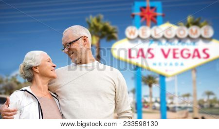 retirement, vacation, tourism and travel concept - happy senior couple hugging over welcome to fabulous las vegas sign background