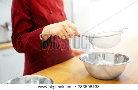 cooking food, baking and people concept - chef with strainer sieving flour into bowl and making batter or dough