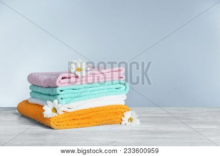 Stack of clean towels with flowers on table against grey background. Laundry day