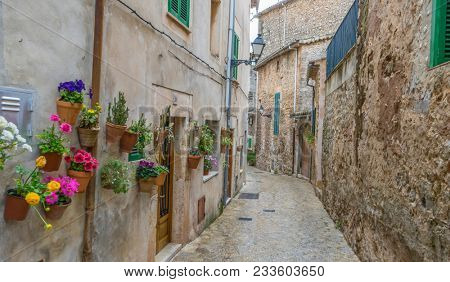 Travel Beautiful street in Valldemossa with traditional flower decoration, famous old mediterranean village of Majorca. Balearic island Mallorca, Spain