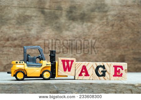 Yellow Toy Forklift Hold Letter Block W To Complete Word Wage On Wood Background