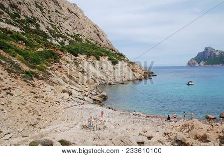 MAJORCA, SPAIN - SEPTEMBER 3, 2017: People enjoy the secluded beach at Cala de Boquer on the Spanish island of Majorca. The beach lies at the end of the Boquer valley in the Tramuntana mountains.