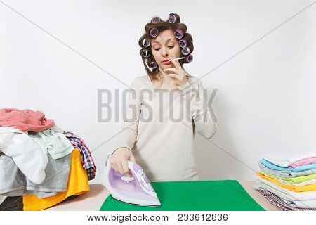Distressed housewife in light clothes with curlers on hair talking on mobile phone, ironing family clothing on ironing board with iron. Woman isolated on white background Copy space for advertisement poster