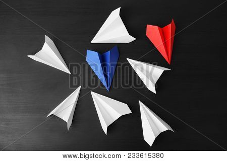 Blue and red paper planes among white ones on dark background. Difference and uniqueness concept