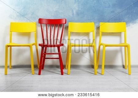 One red chair among yellow ones in room. Difference and uniqueness concept