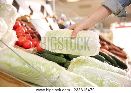 Young woman choosing fresh napa cabbage in supermarket