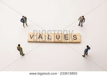 Miniature Figures Businessman : Meeting On Values Letters By Wooden Block Word On White Paper Backgr