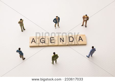 Miniature Figures Businessman : Meeting On Agenda Letters By Wooden Block Word On White Paper Backgr