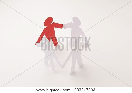 Closed Joining Of Four Paper Figure With Red One In Hand Down Posture On Bright White Background. In