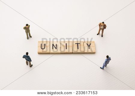 Miniature Figures Businessman : Meeting On Unity Letters By Wooden Block Word On White Paper Backgro