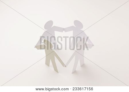 Closed Joining Of Four Paper Figure With Gray One In Hand Down Posture On Bright White Background. I