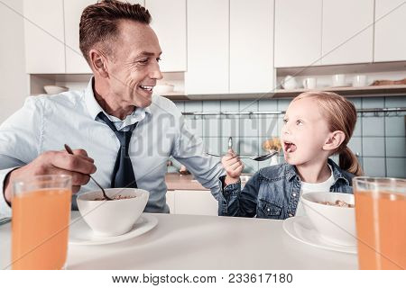 It Is Tasty. Funny Kid Opening Mouth While Eating Breakfast, Looking At Her Daddy While Sitting In T
