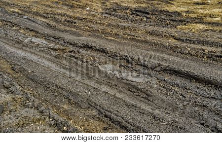 Closeup Of Country Dirt Road. Background Texture Of Dark Brown Road Dirt With Tire Tracks. Mud Road.