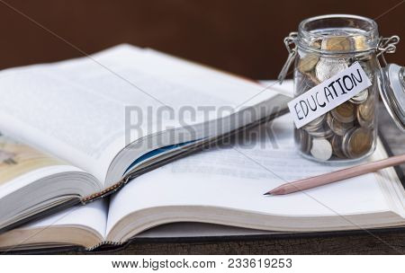 Open Hardback Or Textbook Stacked And A Glass Bottle On The Table. The Concept Of Intelligence Comes