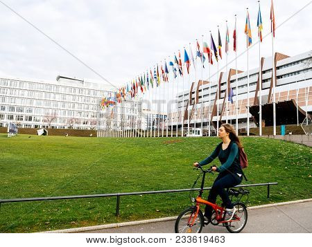 Strasbourg, France - Mar 29, 2018: Woman On Bike In Front Of Council Of Europe With Flag Of Russia F