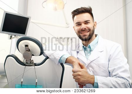 A Young Cheerfull Male Dentist In The Dentist Office