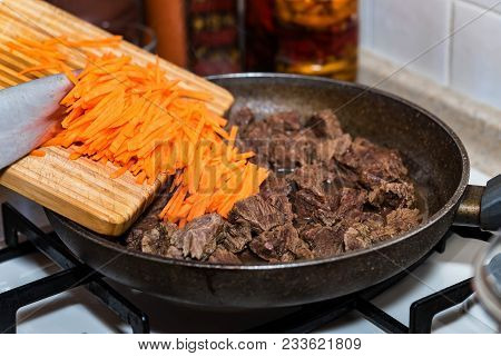 Close-up Adding Chopped Carrot On Frying Pan With Beef Stew