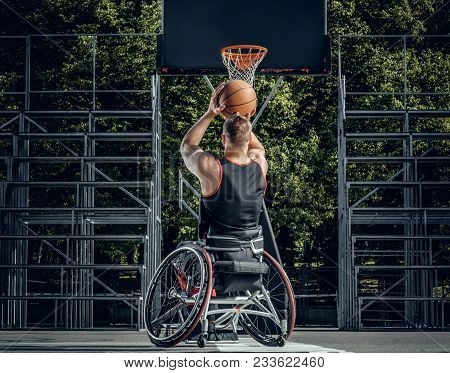 Cripple Basketball Player In Wheelchair Plays Basketball On Open Air Ground.