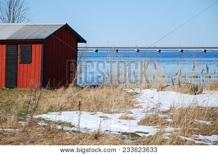 Red Cabin By Spring Season With The Swedish Oland Bridge In The Background