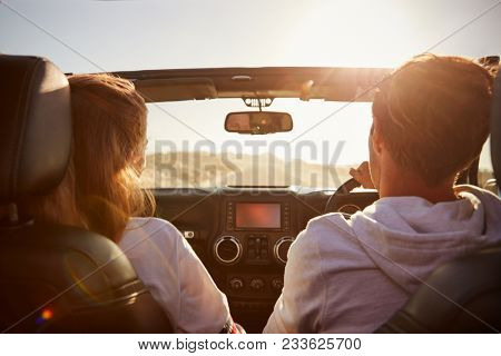 Young couple driving with sunroof open, rear passenger POV